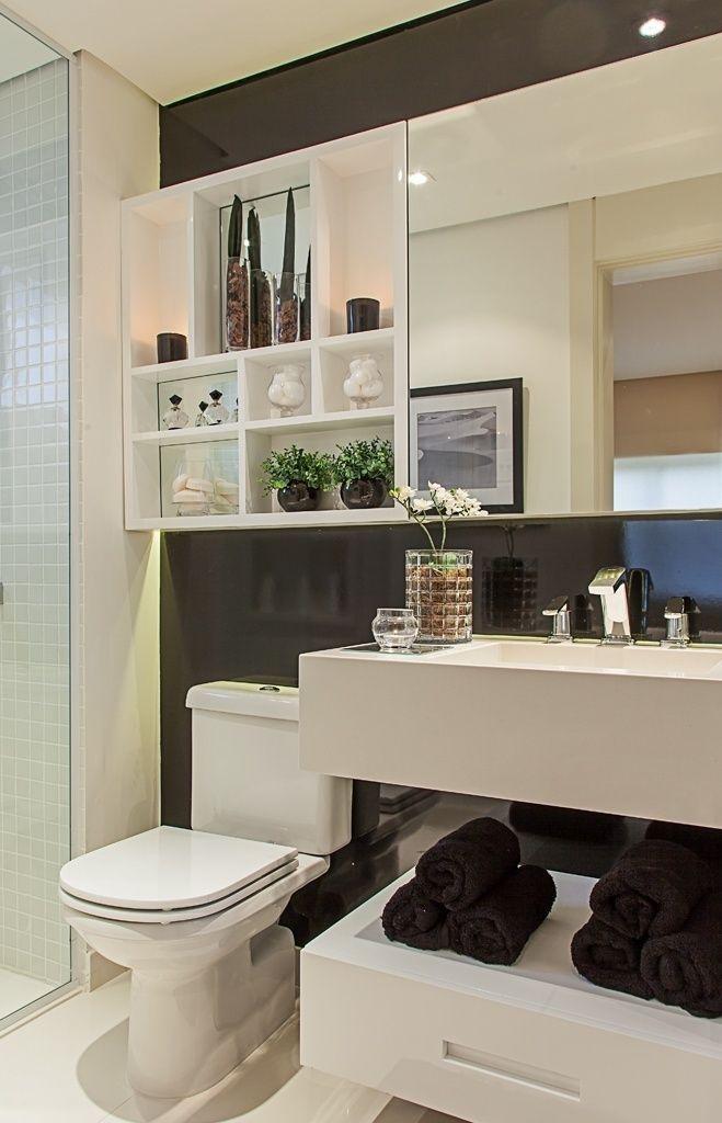 Banheiro preto e branco decorado com nichos de diferentes tamanhos.