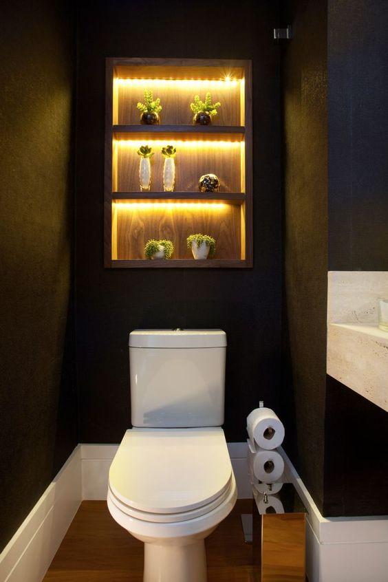 Banheiro escuro com três nichos iluminados decorados com plantas.