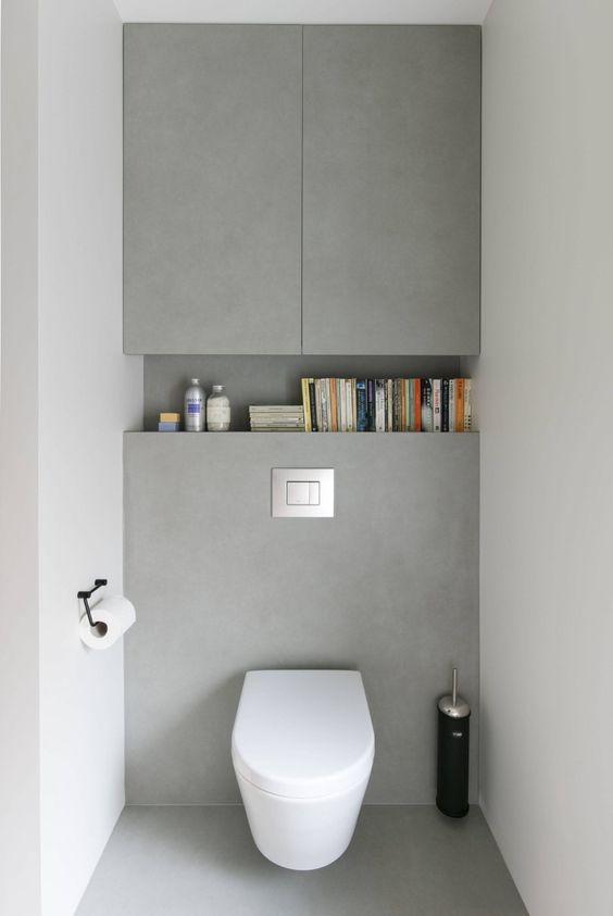 Banheiro com nicho decorado com livros.
