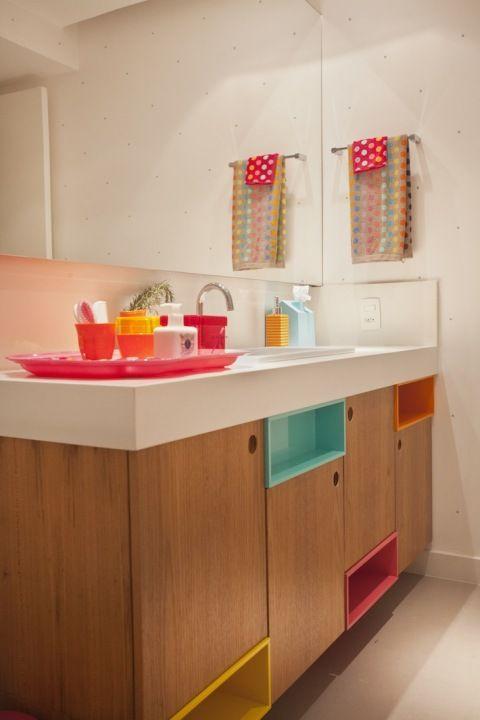 Banheiro colorido com nichos embutidos no armário da pia.