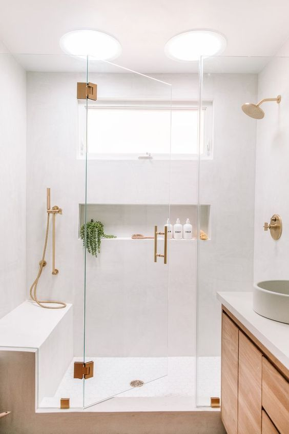 Banheiro com nicho embutido decorado com vaso de planta dentro do box.
