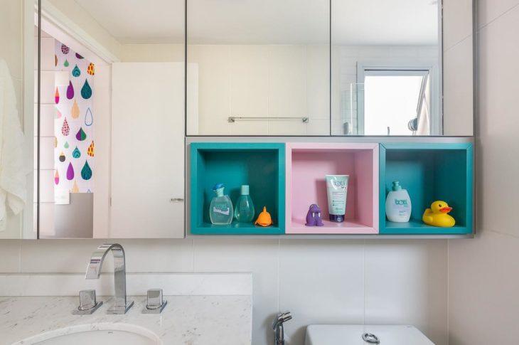 Banheiro com nicho rosa e azul em cômodo infantil.