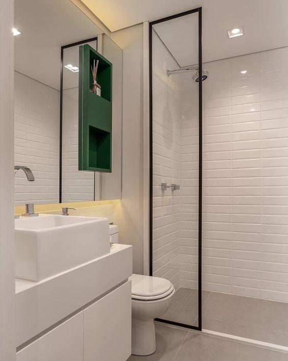 Banheiro com nicho embutido em cima do vaso.