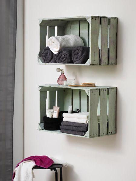 Banheiro com nicho caseiro pintados de branco e decorados com toalhas.