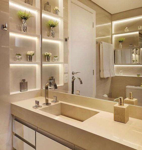 Banheiro com nicho com iluminação interna decorados com perfume e vasos de plantas.
