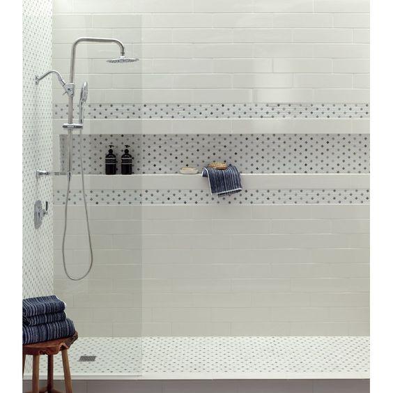 Banheiro branco com nicho revestido de material branco com bolinhas.
