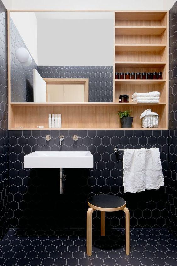 Banheiro com nicho embutido na parede do lado direito e embaixo do espelho.
