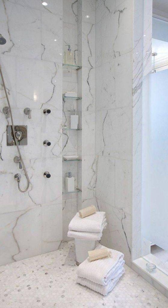 Banheiro com nicho embutido com divisórias de vidro dentro do box.