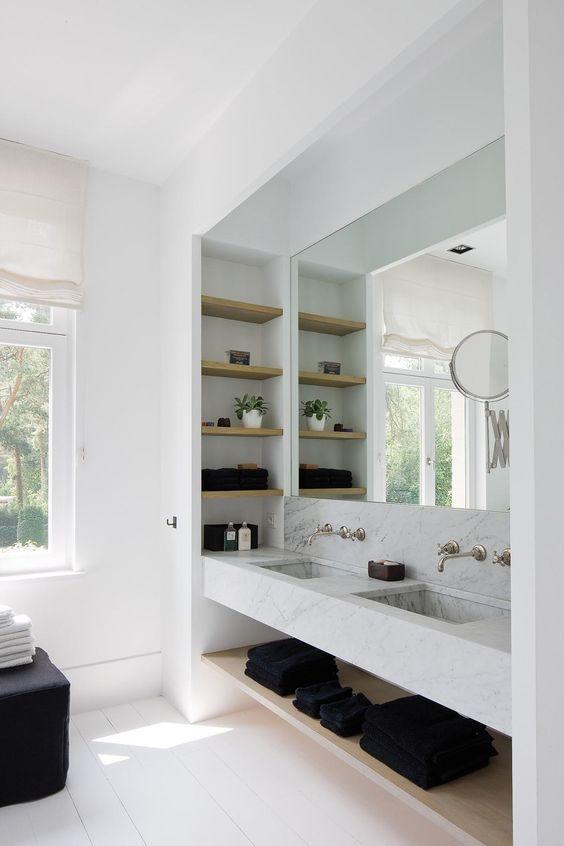 Banheiro com nicho embutido decorado com toalhas pretas e vaso de planta.