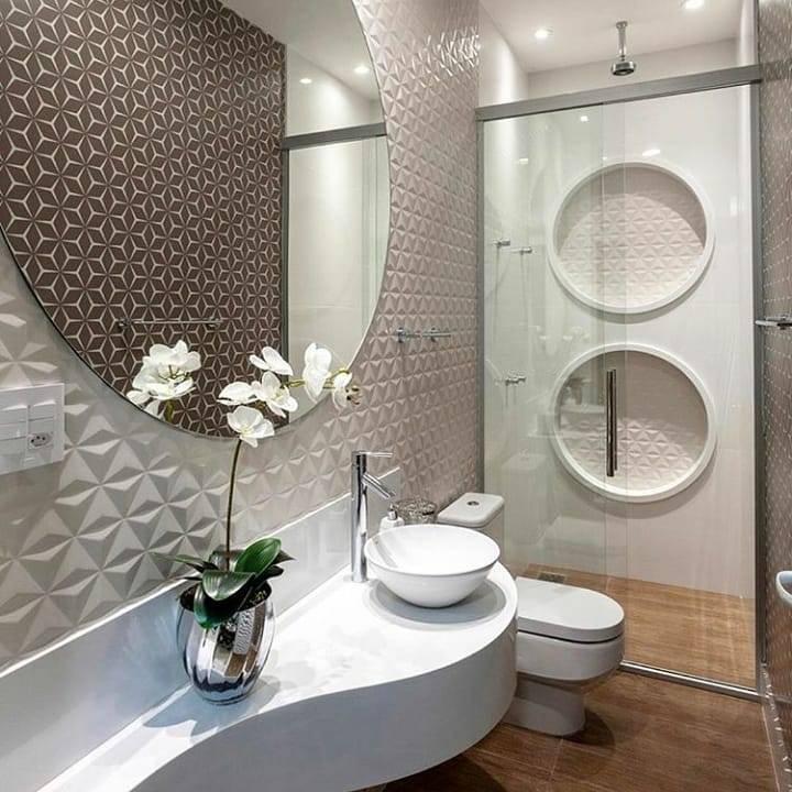 Banheiro com nicho redondo com revestimento texturizado dentro do box.