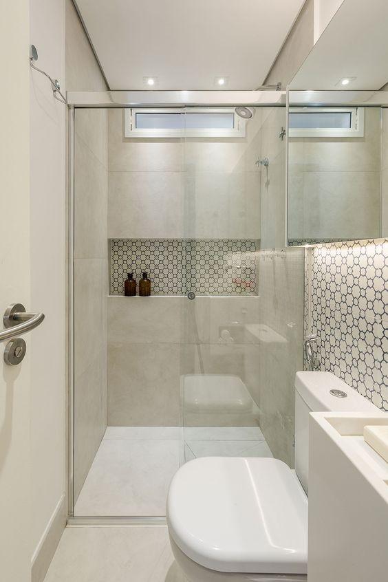 Banheiro com nicho embutido com revestimento em preto e branco.