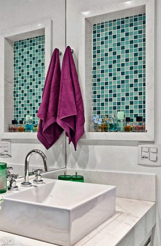 Banheiro com nicho revestido de pastilhas verdes e decorados com perfumes.