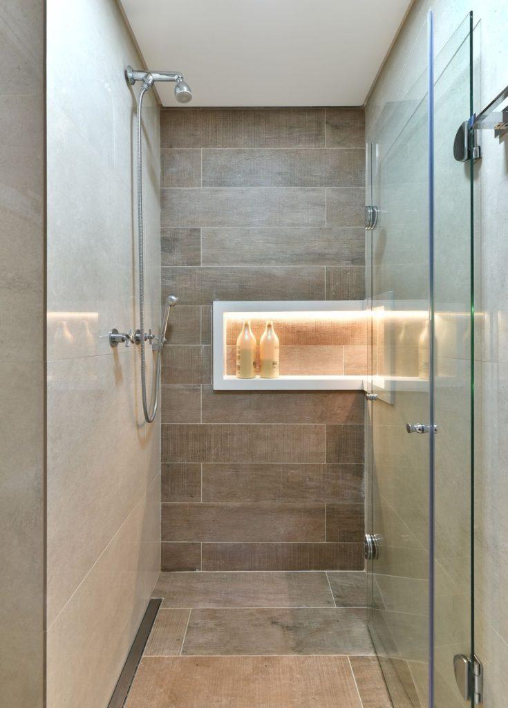 """Banheiro com nicho embutido iluminado em """"L""""."""