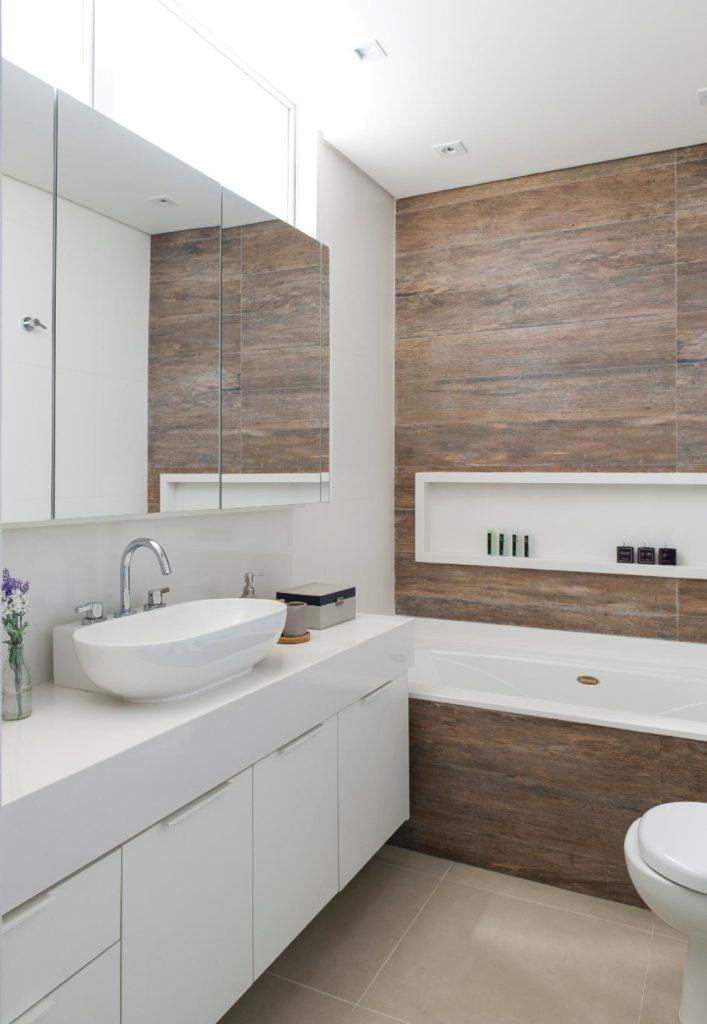 Banheiro com nicho branco e parede amadeirada.