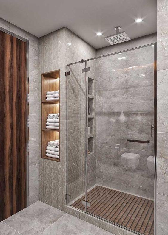 Banheiro cinza com nichos de madeira decorados com toalhas brancas.