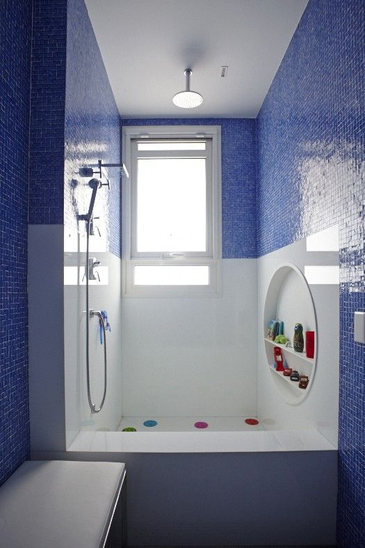 Banheiro azul com nicho redondo dentro do box e artigos coloridos.