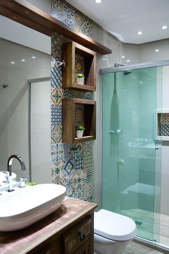 Banheiro com nicho de madeira decorado com plantas em cima do vaso.