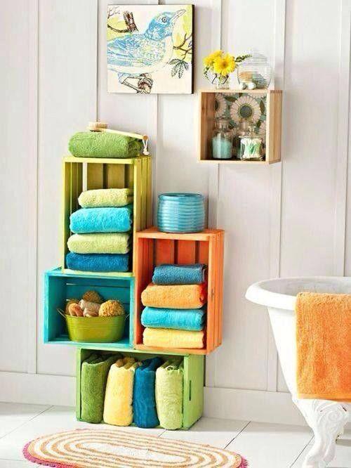 Banheiro com caixotes organizadores de toalhas e um nicho na parede.