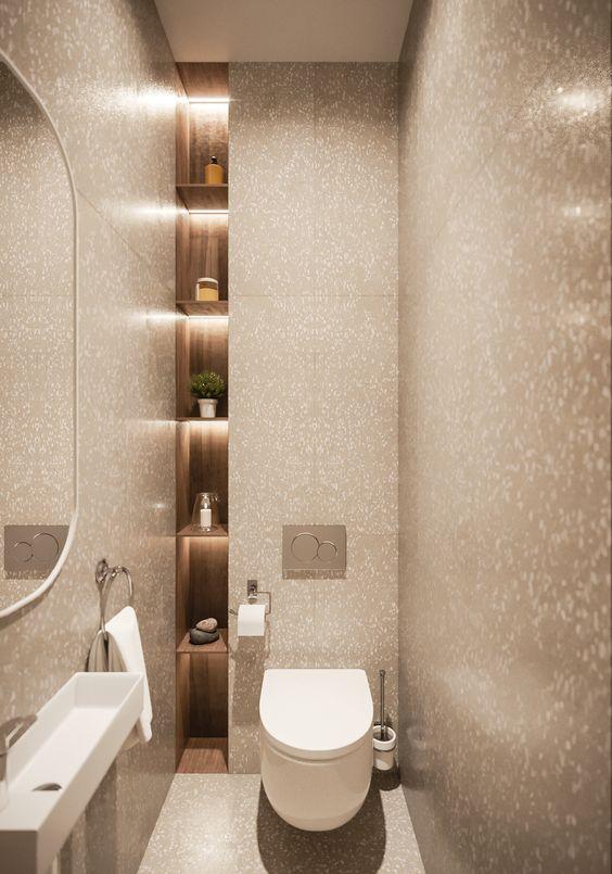 Banheiro com grande nicho dividido com prateleiras de madeira.