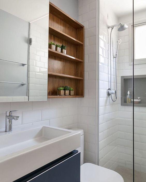 Banheiro com nicho de madeira e parede revestida de azulejo branco.