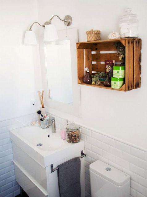 Banheiro branco decorado com nicho de caixote de madeira.
