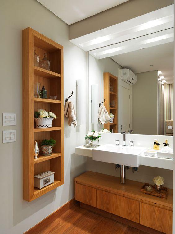 Banheiro com nicho de madeira com diferentes artigos decorativos.