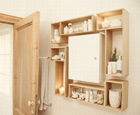 Banheiro com nichos de madeira em diferentes posições decorados com artigos brancos.