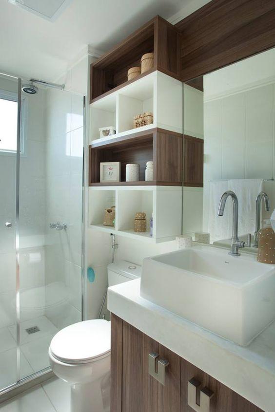 Banheiro com nichos de madeira em cor natural e branco.
