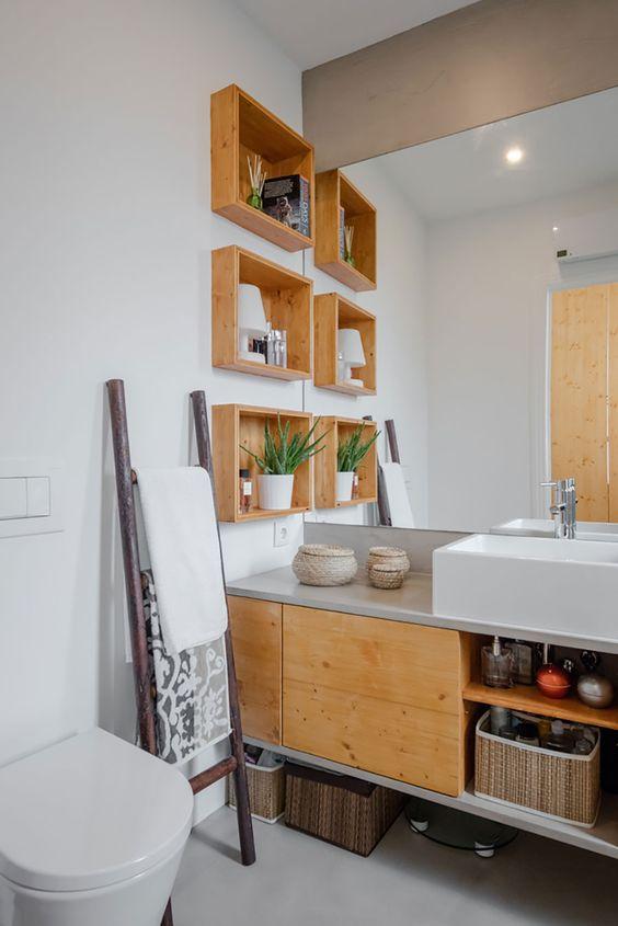 Banheiro com nicho organizador ao lado de uma escada decorativa.