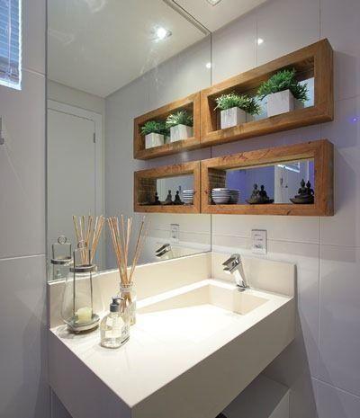 Banheiro com nicho com fundo espelhado ao lado da pia.