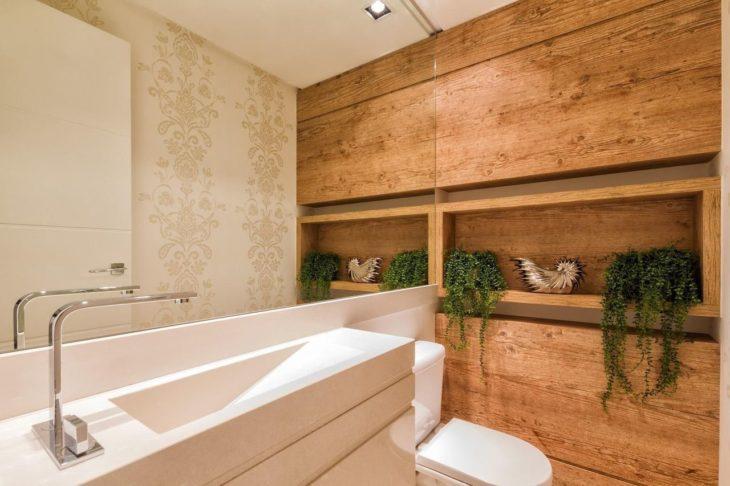 Banheiro com nicho de madeira decorado com plantas.