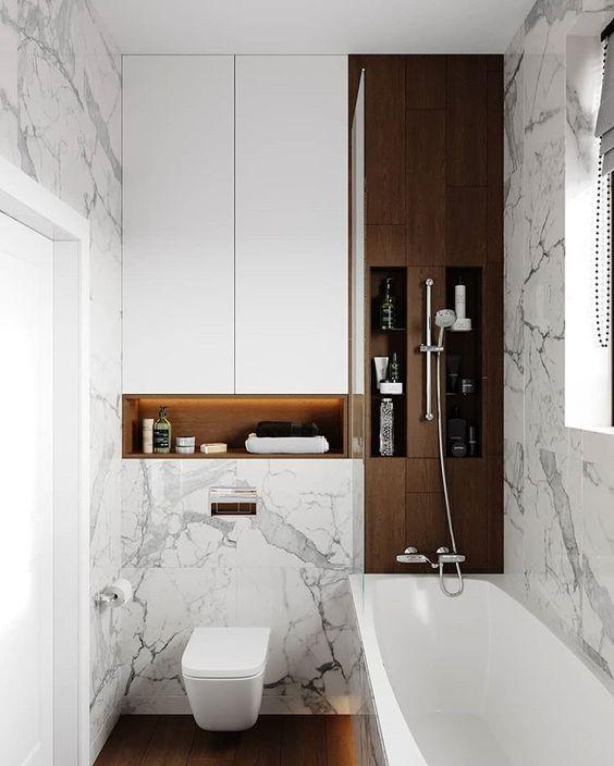 Banheiro com nicho organizador embutido ao lado na banheira e em cima do vaso.