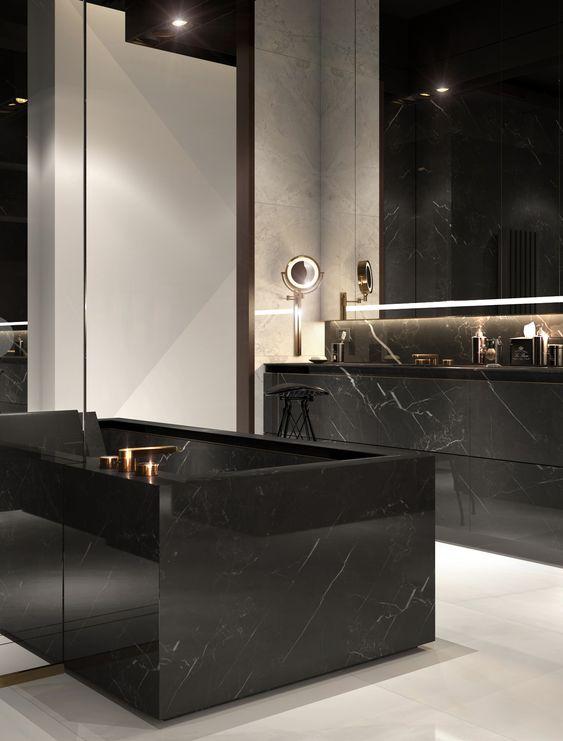 banheiro com banheira e pia em mármore preto