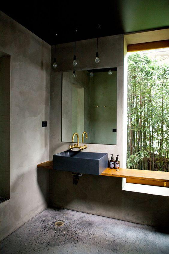 Banheiro moderno com paredes de cimento queimado e teto verde