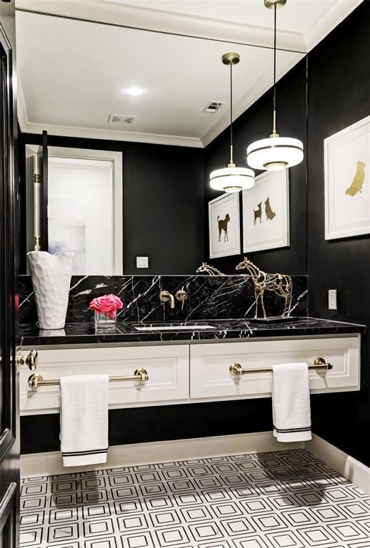 Banheiro preto e branco decorado com quadros e escultura de animais.
