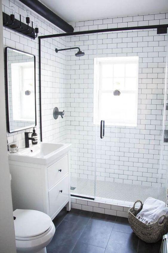 Banheiro com paredes brancas e chão preto.