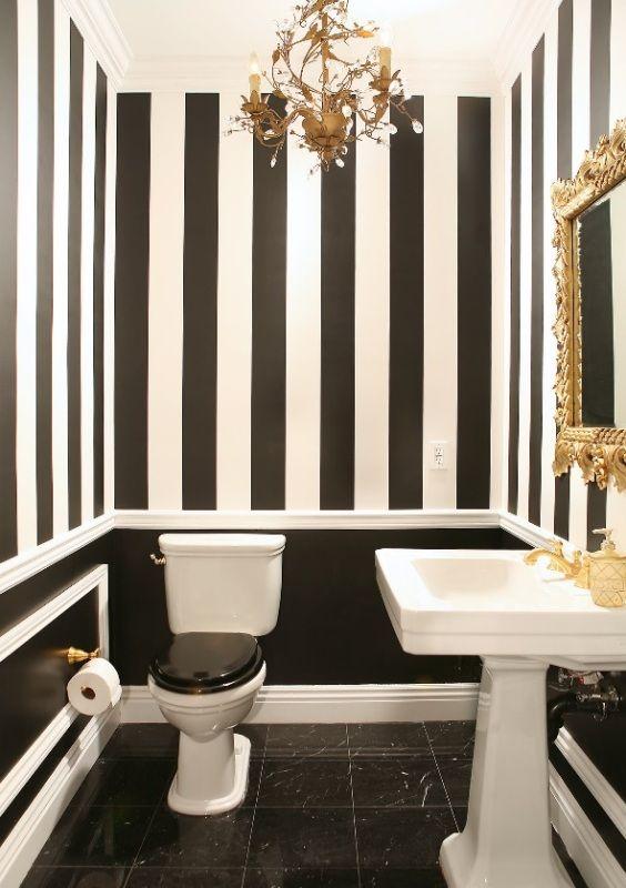 Banheiro com listras pretas e brancas nas paredes e detalhes dourados.