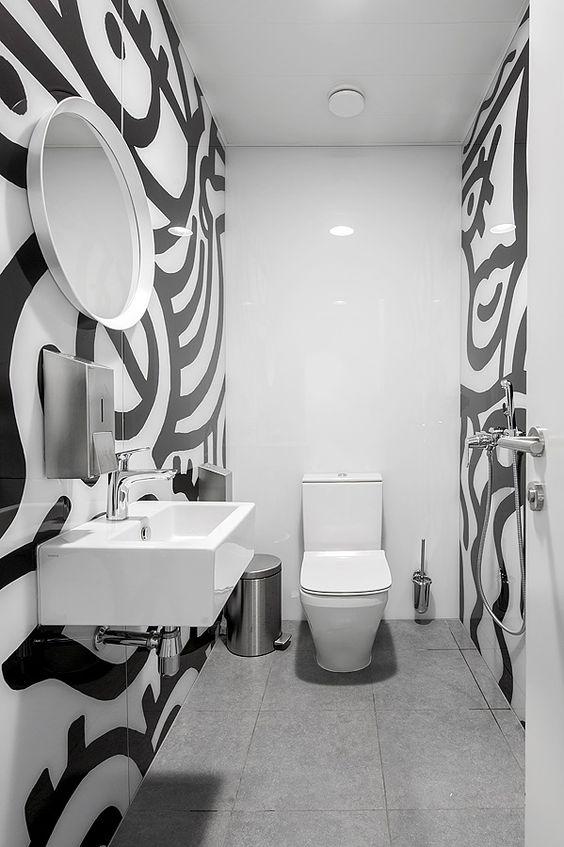 Banheiro branco com desenhos pretos nas paredes laterais.