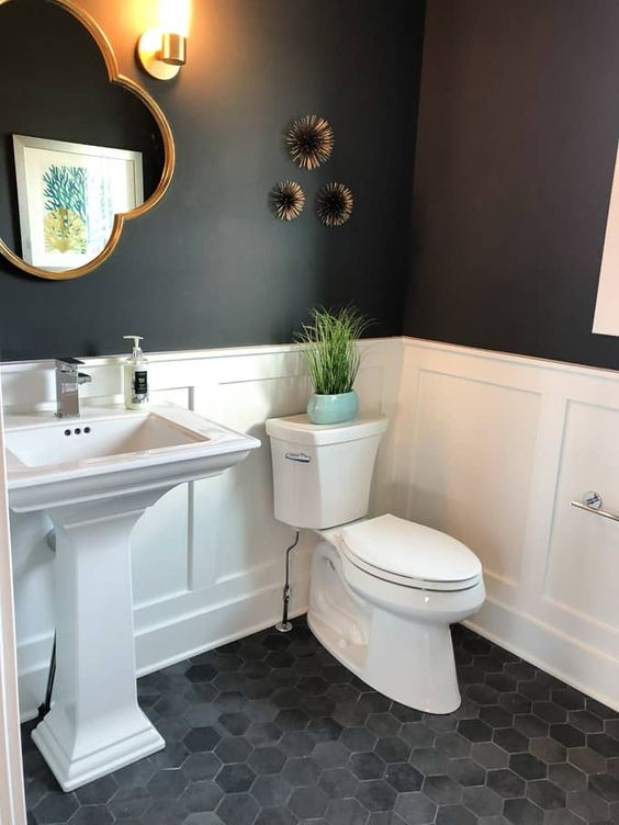 Banheiro decorado com vaso de plantas, artigos na parede e espelho em formato diferente.
