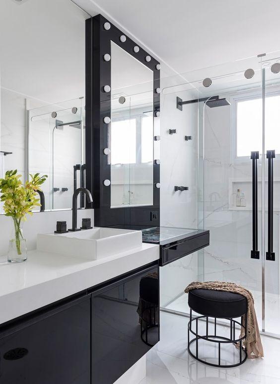 Banheiro branco com armário, banco e moldura do espelho pretos.