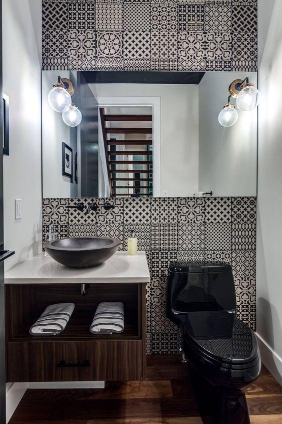 Banheiro com azulejos retrô em preto e branco.