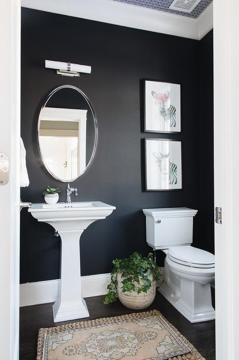 Banheiro com parede e chão pretos e pia com vaso brancos.