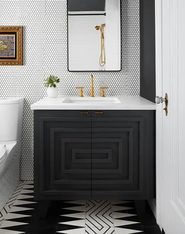 Banheiro com revestimentos diferentes nas paredes e no chão com desenhos preto e branco.
