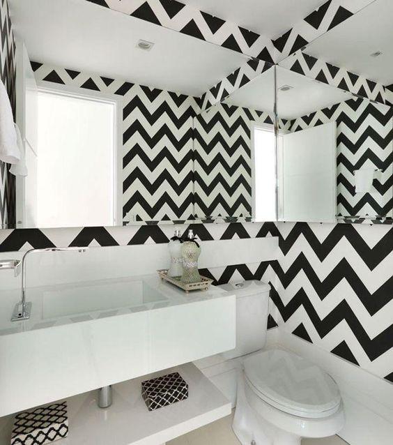 Banheiro com paredes espelhadas e revestimentos de cores intercaladas.