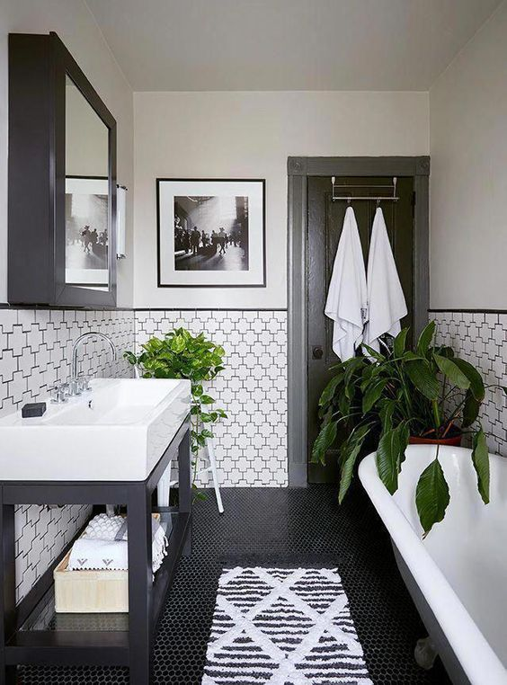 Banheiro preto e branco com revestimento nas paredes que parecem quebra-cabeças.