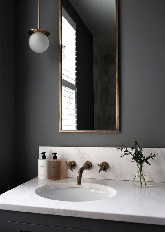 Banheiro decorado com iluminação suspensa e vaso de planta na pia.