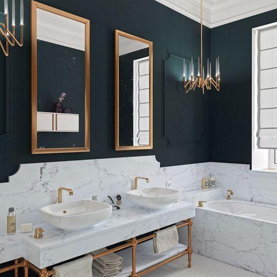 Banheiro preto e branco com detalhes dourados no espelho, no lustre, nas torneiras e no suporte da pia.