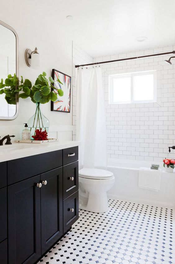 Banheiro branco com armário preto e piso mesclado.