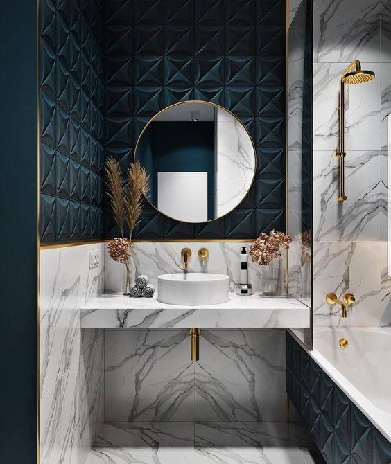Banheiro decorado com detalhes dourados e vasos com planta e flores na pia.