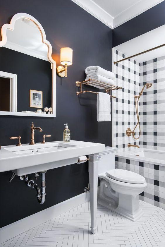 Banheiro preto e branco com detalhes dourados.